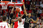 North Carolina State's DJ Funderburk (0) tries to split the defense of Florida State's Malik Osborne (10) and Devin Vassell (24) during the second half of an NCAA college basketball game in Raleigh, N.C., Saturday, Feb. 22, 2020. (AP Photo/Karl B DeBlaker)