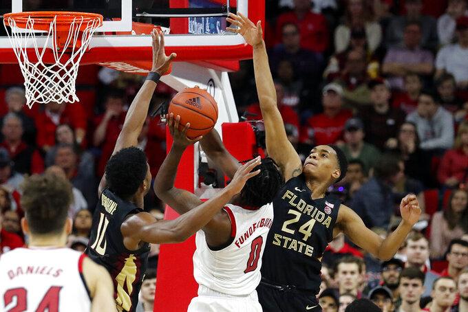 North Carolina State's DJ Funderburk (0) tries to split the defense of Florida State's Malik Osborne (10) and Devin Vassell (24) during the second half of an NCAA college basketball game in Raleigh, N.C., Saturday, Feb. 22, 2020. (AP Photo/Karl B DeBlaker)