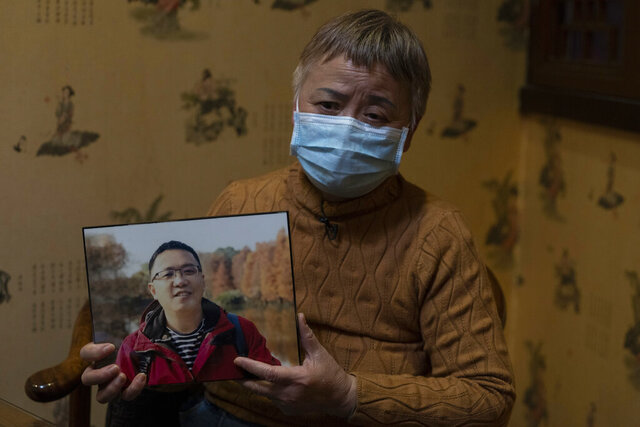 "Zhong Hanneng holds a photo of her son, Peng Yi, and talks about his difficulties in getting tested for COVID-19, eventually dying from the disease, in Wuhan in central China's Hubei province on Saturday, Oct. 17, 2020. ""There were very, very few tests, basically none. ... if you couldn't prove you were positive, you couldn't get admitted to a hospital. ... The doctor said there was nothing that could be done."" (AP Photo/Ng Han Guan)"