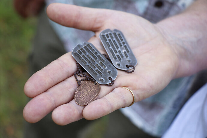 FILE - In this Aug. 3, 2017, file photo, the dog tags and a Hawaiian pressed penny charm of Pfc. Dale W. Ross are displayed at Guadalcanal in the Solomon Islands. The U.S. Defense POW/MIA Accounting Agency has positively identified skeletal remains recovered two years ago on the Solomon Islands in the South Pacific as those of Pfc. Dale W. Ross, whose surviving family lives in Ashland, Oregon. (Justin Taylan/Pacific Wrecks via AP, File)