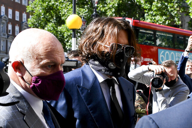 Johnny Depp, right, wearing a protective mask arrives at the Royal Court of Justice, in London, Tuesday, July 7, 2020. Johnny Depp is suing a tabloid newspaper for libel over an article that branded him a
