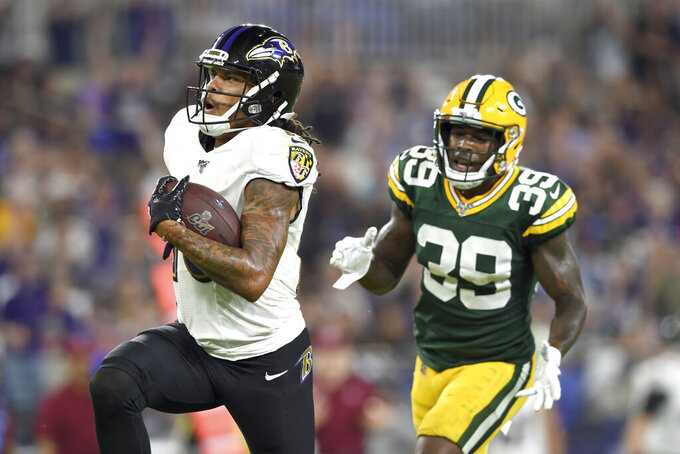 Baltimore Ravens wide receiver Chris Moore, left, runs in a touchdown catch on a pass from quarterback Trace McSorley, not visible, as Green Bay Packers defensive back Chandon Sullivan (39) chases him during the first half of a NFL football preseason game, Thursday, Aug. 15, 2019, in Baltimore. (AP Photo/Gail Burton)