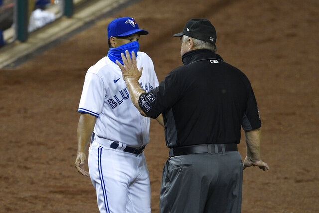 Toronto Blue Jays manager Charlie Montoyo, left, talks with first base umpire Joe West, right, after Rowdy Tellez was ejected during the tenth inning of a baseball game against the Washington Nationals, Wednesday, July 29, 2020, in Washington. The Nationals won 4-0 in extra innings. (AP Photo/Nick Wass)