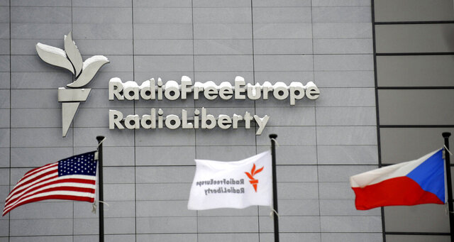 FILE - In this Jan. 15, 2010, file photo, the headquarters of Radio Free Europe/Radio Liberty is seen with U.S., RFE/RL and the Czech Republic flags in the foreground in Prague. The heads of three federally-funded international broadcasters were abruptly fired late Friday, Jan. 22, 2021, as the Biden administration completed a house-cleaning of Donald Trump appointees at the U.S. Agency for Global Media. Two officials familiar with the changes said the acting chief of the USAGM summarily dismissed the directors of Radio Free Europe/Radio Liberty, Radio Free Asia and the Middle East Broadcasting Networks just a month after they had been named to the posts. (Michal Kamaryt/CTK via AP, File)