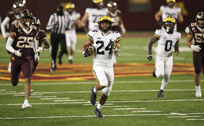 Michigan running back Zach Charbonnet (24) carries for a touchdown against Minnesota in the first half of an NCAA college football game Saturday, Oct. 24, 2020, in Minneapolis. (Mark Vancleave/Star Tribune via AP)
