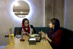 In this Monday, Oct. 7, 2019 photo, two Iranians eat at an Afghan cafe in downtown Tehran, Iran. More than 3 million Afghans including as many as 2 million who entered without legal permission, live in the Islamic Republic, according to United Nations estimates. Hamed Azar and his business partner, 21-year-old Afghan refugee Fatemeh Jafari, raised money from their parents, as well as used their own cash to open their Telma, or
