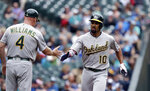 Oakland Athletics' Marcus Semien (10) is congratulated on his solo home run by third base coach Matt Williams in the second inning of a baseball game against the Seattle Mariners  Sunday, July 7, 2019, in Seattle. (AP Photo/Elaine Thompson)