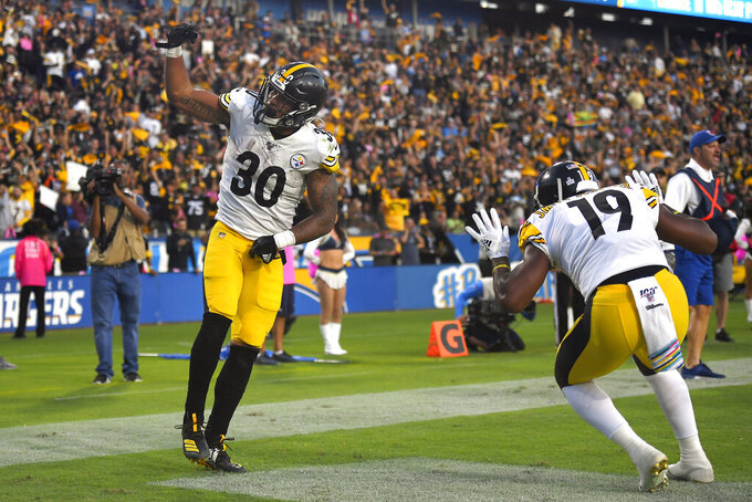 Pittsburgh Steelers running back James Conner, left, celebrates his touchdown with wide receiver JuJu Smith-Schuster during the first half of an NFL football game against the Los Angeles Chargers, Sunday, Oct. 13, 2019, in Carson, Calif. (AP Photo/Kyusung Gong)