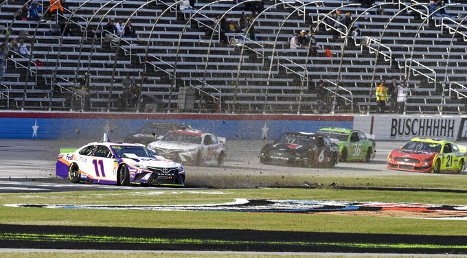 Denny Hamlin (11) wrecks into the grass on the front stretch during a NASCAR Cup Series auto race at Texas Motor Speedway, Sunday, Nov. 3, 2019, in Fort Worth, Texas. (AP Photo/Larry Papke)