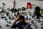 Jonathan Desara waits for customers, backdropped by a wall display of used items, at an open-air market located under a bridge in Caracas, Venezuela, Wednesday, March 20, 2019. (AP Photo/Natacha Pisarenko)