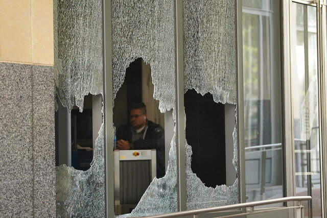 A man sits behind a broken glass from a window at the Ronald V. Dellums Federal Building in Oakland, Calif., Sunday, July 26, 2020. A protest through the streets of downtown Oakland, California, in support of racial justice and police reform turned violent when