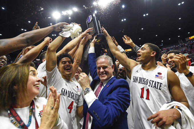 San Diego State head coach Brian Dutcher, center, and players hold up the Mountain West Championship trophy after beating New Mexico 82-59 in an NCAA college basketball game, Tuesday, Feb. 11, 2020, in San Diego. (AP Photo/Denis Poroy)