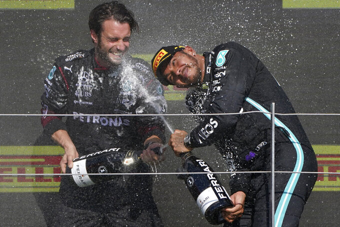 Mercedes driver Lewis Hamilton of Britain, right, celebrates on the podium after winning the British Formula One Grand Prix, at the Silverstone circuit, in Silverstone, England, Sunday, July 18, 2021. (AP Photo/Jon Super)