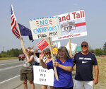 FILE - In this July 8, 2019 file photo, supporters of a fully funded oil check hold signs in Wasilla, Alaska. For decades, Alaska has had an uneasy reliance on oil, building budgets around its volatile boom-or-bust nature. When times were rough, prices always seemed to rebound, forestalling a day of reckoning some believe may finally have come. The situation has politicians weighing changes to the annual dividend paid to residents from earnings of the state's oil-wealth fund, the Alaska Permanent Fund. (AP Photo/Mark Thiessen, File)