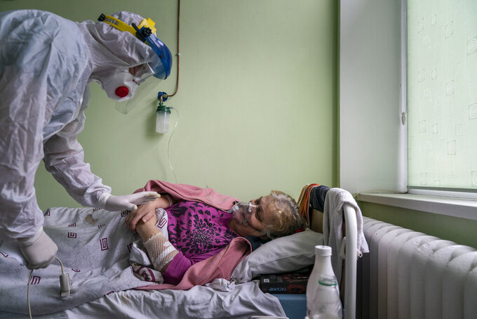 Dr. Oleh Hornostayev speaks to a coronavirus patient at the hospital in Stryi, Ukraine, on Tuesday, Sept. 29, 2020. Coronavirus infections in Ukraine began surging in late summer, and the ripples are hitting towns in the western part of the country. The government wants to avoid imposing a new lockdown, but officials acknowledge that the rising infections could make it necessary. (AP Photo/Evgeniy Maloletka)