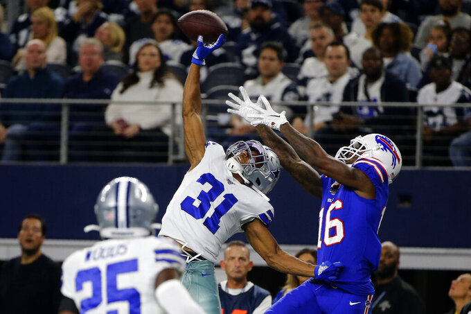 Dallas Cowboys safety Xavier Woods (25) looks on as cornerback Byron Jones (31) breaks up a pass intended or Buffalo Bills wide receiver Robert Foster (16) in the first half of an NFL football game in Arlington, Texas, Thursday, Nov. 28, 2019. (AP Photo/Michael Ainsworth)