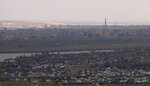 The Islamic State group's last pocket of territory in Baghouz, Syria, as seen from a distance on Sunday, March 17, 2019. U.S.-backers forces fighting to take back the last IS outpost in Syria said they are facing difficulties defeating the group. A spokesman says their effort is being slowed by mines, tunnels, and the possibility of harming women and children still in the village. (AP Photo/Maya Alleruzzo)