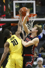 Oregon's Shakur Juiston, left, shoots next to Utah's Branden Carlson during the second half of an NCAA college basketball game in Eugene, Ore., Sunday, Feb. 16, 2020. (AP Photo/Chris Pietsch)
