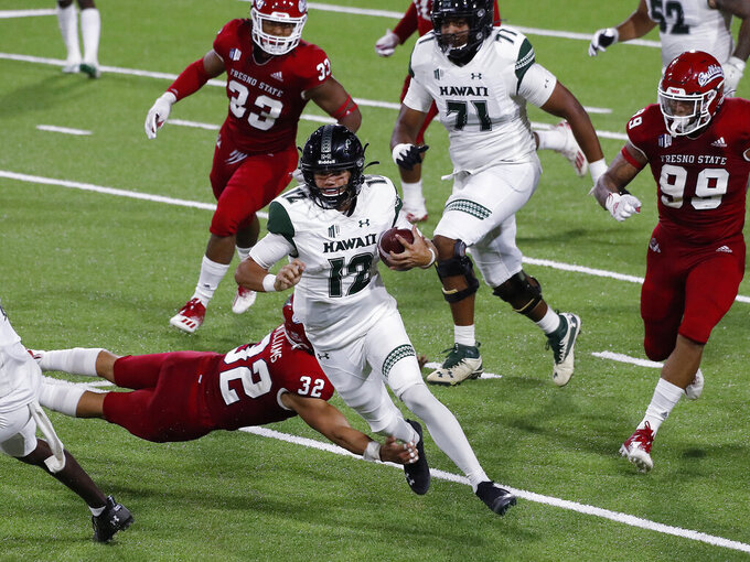 Hawaii quarterback Chevan Cordeiro (12) takes off on a draw play for a big gain against Fresno State defensive back Evan Williams during the second half of an NCAA college football game in Fresno, Calif., Saturday, Oct. 24, 2020. (AP Photo/Gary Kazanjian)