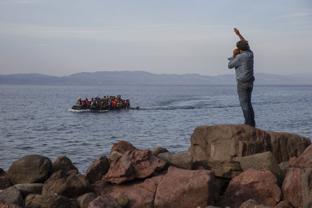 In this Wednesday, Sept. 9, 2015 photo refugees and migrants aboard an overcrowded dinghy as they cross the Aegean Sea, from Turkey, that is seen in the background, to the coast of Lesbos island, Greece.  Greek authorities have invited private contractors to bid on supplying a 2.7-kilometer-long (1.7 miles) floating barrier system aimed at stopping migrants from reaching the country's islands from the nearby coast of Turkey. (AP Photo/Petros Giannakouris)