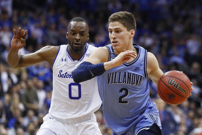 FILE - Villanova's Collin Gillespie (2) drives past Seton Hall's Quincy McKnight (0) during the first half of an NCAA college basketball game in Newark, N.J., in this Wednesday, March 4, 2020, file photo. Gillespie averaged 15.1 points, 4.5 assists, 3.7 rebounds and 1.2 steals last year.(AP Photo/John Minchillo, FIle)
