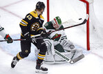 Boston Bruins center Danton Heinen (43) tips the puck past Minnesota Wild goaltender Alex Stalock, right, for a goal during the first period of an NHL hockey game in Boston, Tuesday, Jan. 8, 2019. (AP Photo/Charles Krupa)