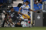 Minnesota United midfielder Hassani Dotson, left, and San Jose Earthquakes defender Nick Lima battle for the ball during the first half of an MLS soccer match, Saturday, Aug. 1, 2020, in Kissimmee, Fla. (AP Photo/John Raoux)