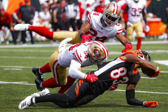 Cincinnati Bengals wide receiver Tyler Boyd (83) is tackled by San Francisco 49ers middle linebacker Fred Warner (54) and defensive back K'Waun Williams (24) during the second half an NFL football game, Sunday, Sept. 15, 2019, in Cincinnati. (AP Photo/Frank Victores)