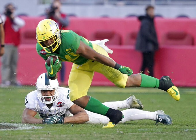 Oregon running back CJ Verdell (34) breaks a tackle by Michigan State safety Khari Willis (27) during the second half of the Redbox Bowl NCAA college football game Monday, Dec. 31, 2018, in Santa Clara, Calif. Oregon won 7-6. (AP Photo/Tony Avelar)