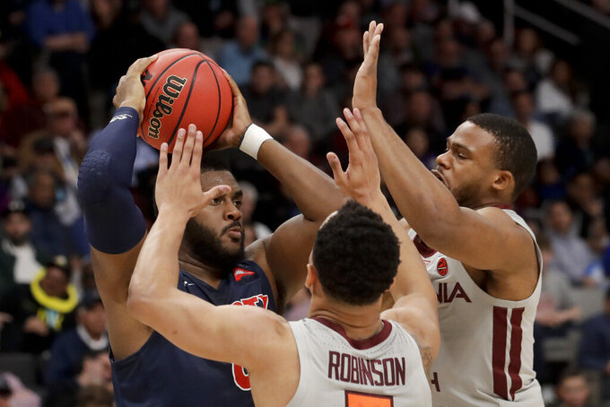 Liberty forward Myo Baxter-Bell, left, is guarded by Virginia Tech guard Justin Robinson (5) and forward P.J. Horne during the first half of a second-round game in the NCAA men's college basketball tournament Sunday, March 24, 2019, in San Jose, Calif. (AP Photo/Jeff Chiu)