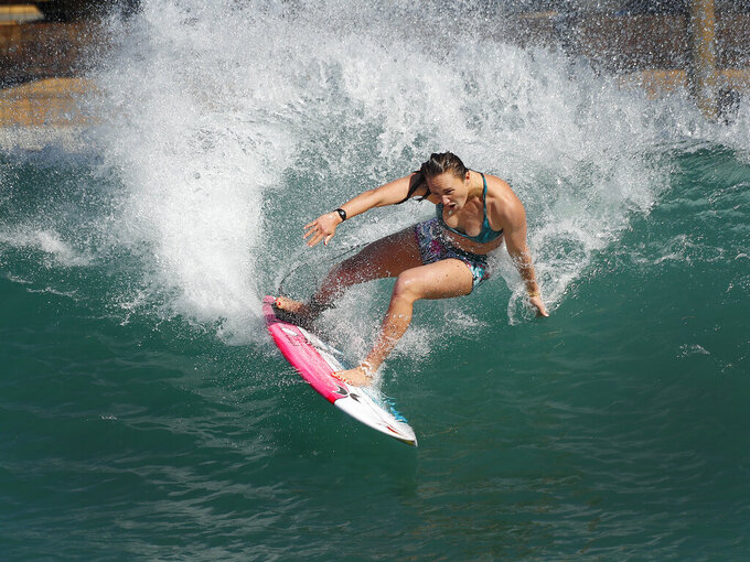Surfer Carissa Moore of the United States works out on a Surf Ranch wave during practice rounds for the upcoming Olympics Yuesday, June 15, 2021, in Lemoore, Calif. Moore is headed to the Olympics for surfing's debut at the Games, Though there's much excitement and renewed enthusiasm for the women's game, the objectification, pay disparities and opportunity gap have taken its toll. Industry leaders say they're committed to righting the wrongs that have long held female surfers back in the male-dominated sport. The mental, financial and logistical roadblocks for women in surfing date back centuries. (AP Photo/Gary Kazanjian)