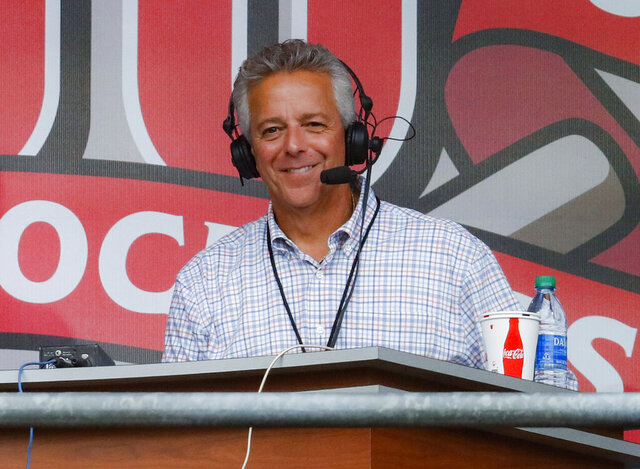 FILE - In this Sept. 25, 2019, file photo, Cincinnati Reds broadcaster Thom Brennaman sits in a special outside booth before the Reds' baseball game against the Milwaukee Brewers in Cincinnati. The Reds say Brennaman has resigned following his use of an anti-gay slur on air in August. (AP Photo/John Minchillo, File)