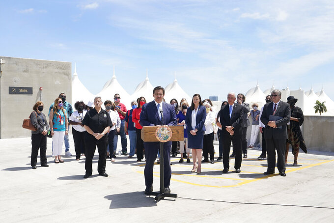 Florida Gov. Ron DeSantis, center, speaks during a news conference surrounded by cruise workers, Thursday, April 8, 2021, at PortMiami in Miami. DeSantis announced a lawsuit against the federal government and the CDC demanding that cruise ships be allowed to sail. (AP Photo/Wilfredo Lee)