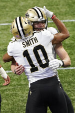 New Orleans Saints wide receiver Tre'Quan Smith (10) embraces New Orleans Saints quarterback Taysom Hill (7) after Smith scored a touchdown on a catch against the Atlanta Falcons during the first half of an NFL football game, Sunday, Dec. 6, 2020, in Atlanta. (AP Photo/John Bazemore)