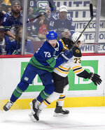 Vancouver Canucks' Tyler Toffoli, left, and Boston Bruins' Charlie McAvoy collide during the second period of an NHL hockey game Saturday, Feb. 22, 2020, in Vancouver, British Columbia. (Darryl Dyck/The Canadian Press via AP)