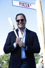 Former New York Mets catcher Mike Piazza poses for a photo under a street sign for newly named Piazza Dr., after a ceremony in front of the Mets spring training facility, Thursday, Jan. 16, 2020, in Port St. Lucie, Fla. (AP Photo/Wilfredo Lee)