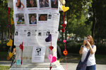 A woman takes a photo of a plinth covered with images of victims during a tribute for murdered women, in the Alameda park of Mexico City, Saturday, Aug. 24, 2019. A small group of women constructed a memorial made of hand-knit hearts. The knit-in on came on the heels of rowdy protests sparked by outrage over bungled investigations into alleged rapes of teenagers by local policemen. (AP Photo/Ginnette Riquelme)