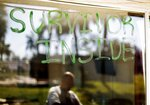 Shawn Gehlert is reflected in a message displayed on a window of his motel room, Tuesday, Oct. 16, 2018, in Panama City, Fla., where survivors continue to live amid the damage from Hurricane Michael. (AP Photo/David Goldman)