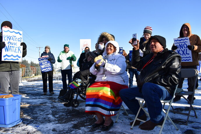 Opponents of the Keystone XL oil pipeline from Canada are seen demonstrating in sub-freezing temperatures on Tuesday, Oct. 29, 2019 in Billings, Mont. The State Department has released a new environmental study of the long-stalled, $8 billion project. (AP Photo/Matthew Brown)
