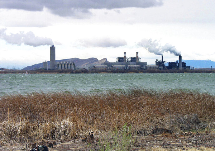 FILE - This April, 2006, file photo shows the Four Corners Power Plant in Waterflow, N.M., near the San Juan River in northwestern New Mexico. The closure of the coal-fired power plant on the Navajo Nation sooner than expected will be a major blow to a region where coal has been a mainstay of the economy for decades. Arizona Public Service Co. now plans to shutter the Four Corners Power Plant in 2031 when its coal contract expires rather than wait until 2038. (AP Photo/Susan Montoya Bryan, File)