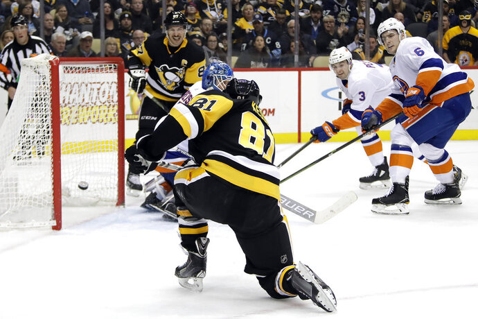 Pittsburgh Penguins' Phil Kessel (81) gets the puck behind New York Islanders goaltender Thomas Greiss for the first of his two goals of the second period in an NHL hockey game in Pittsburgh, Thursday, Dec. 6, 2018. (AP Photo/Gene J. Puskar)