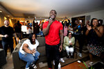 Oklahoma running back Rhamondre Stevenson, center, is reacts with family and friends in a suite at the Aria Resort in Las Vegas, Saturday, May 1, 2021, after he was selected in the fourth round of the NFL football draft by the New England Patriots. (Steve Marcus/Las Vegas Sun via AP)