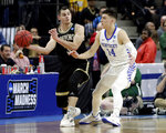 Wofford's Fletcher Magee, left, passes the ball around Kentucky's Tyler Herro (14) during the first half of a second-round game in the NCAA men's college basketball tournament in Jacksonville, Fla., Saturday, March 23, 2019. (AP Photo/John Raoux)