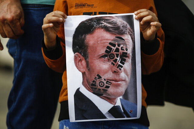 A child holds a photograph of France's President Emmanuel Macron, stamped with a shoe mark, during a protest against France in Istanbul, Sunday, Oct. 25, 2020. Turkish President Recep Tayyip Erdogan on Sunday challenged the United States to impose sanctions against his country while also launching a second attack on French President Emmanuel Macron. Speaking a day after he suggested Macron needed mental health treatment because of his attitude to Islam and Muslims, which prompted France to recall its ambassador to Ankara, Erdogan took aim at foreign critics. (AP Photo/Emrah Gurel)