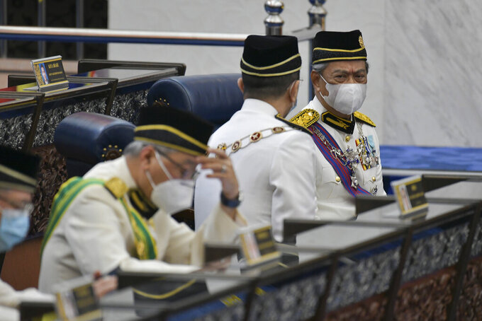 In this photo released by Malaysia's Department of Information, Malaysia's Prime Minister Muhyiddin Yassin, right, wearing a face mask along with his cabinet members attend the opening ceremony of the third term of the 14th parliamentary session at parliament house in Kuala Lumpur Monday, May 18, 2020.  Malaysia's parliament held an unusual half-day sitting Monday, that was kept short due to the COVID-19 pandemic and saw Prime Minister Muhyiddin Yassin dodge a vote of no-confidence against him over two months since he came into power. (Nazri Rapai/Malaysia's Department of Information via AP)