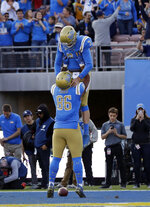 UCLA quarterback Wilton Speight, top, celebrates his rushing touchdown with teammate Devin Asiasi during the second half of an NCAA college football game against Stanford Saturday, Nov. 24, 2018, in Pasadena, Calif. (AP Photo/Marcio Jose Sanchez)