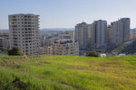 In this Tuesday, April 28, 2020 photo, apartment towers loom over the West Bank village of Kufr Aqab. As the coronavirus pandemic gathered strength in April, community leaders in Kufr Aqab, a Palestinian neighborhood on the outskirts of Jerusalem, tried to impose lockdown and quarantine measures to protect residents. The problem: There are no police. Kufr Aqab is within city boundaries drawn up by Israel, but it's on the opposite side of Israel's separation barrier. That means neither the Israeli police nor Palestinian security forces are able to operate there. (AP Photo/Nasser Nasser)