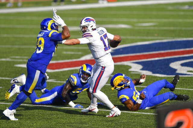 Los Angeles Rams' Aaron Donald, left, rushes Buffalo Bills quarterback Josh Allen during the second half of an NFL football game Sunday, Sept. 27, 2020, in Orchard Park, N.Y. Allen was called for a face mask penalty on the play. The Bills won 35-32. (AP Photo/Adrian Kraus)