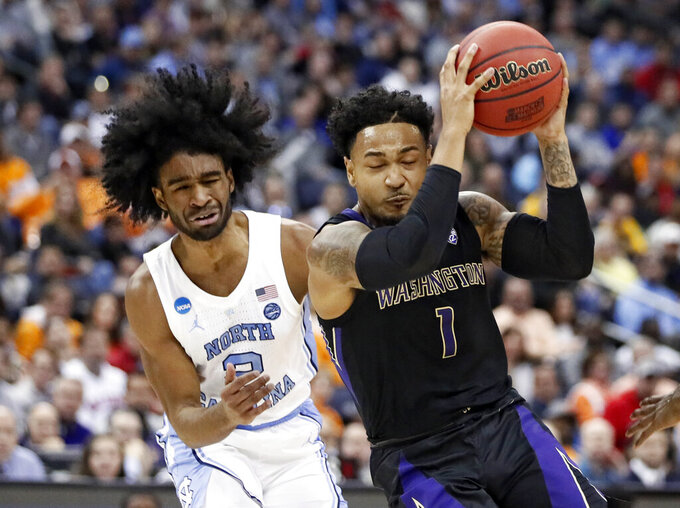 Washington's David Crisp (1) drives past North Carolina's Coby White (2) in the first half during a second round men's college basketball game in the NCAA Tournament in Columbus, Ohio, Sunday, March 24, 2019. (AP Photo/John Minchillo)