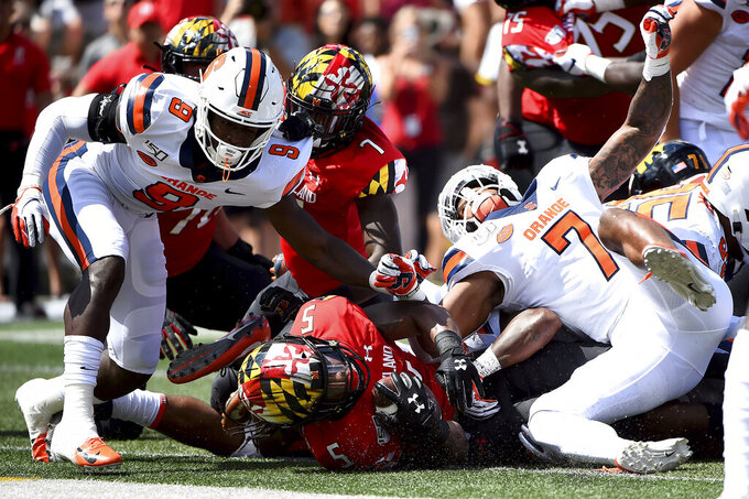 Maryland Terrapins running back Anthony McFarland Jr. (5) falls in to the end zone for a touchdown in front of Syracuse Orange defenders during the first half of an NCAA college football game, Saturday, Sept. 7, 2019, in College Park, Md. (AP Photo/Will Newton)
